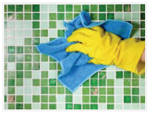 A gloved hand cleaning tile with a towel